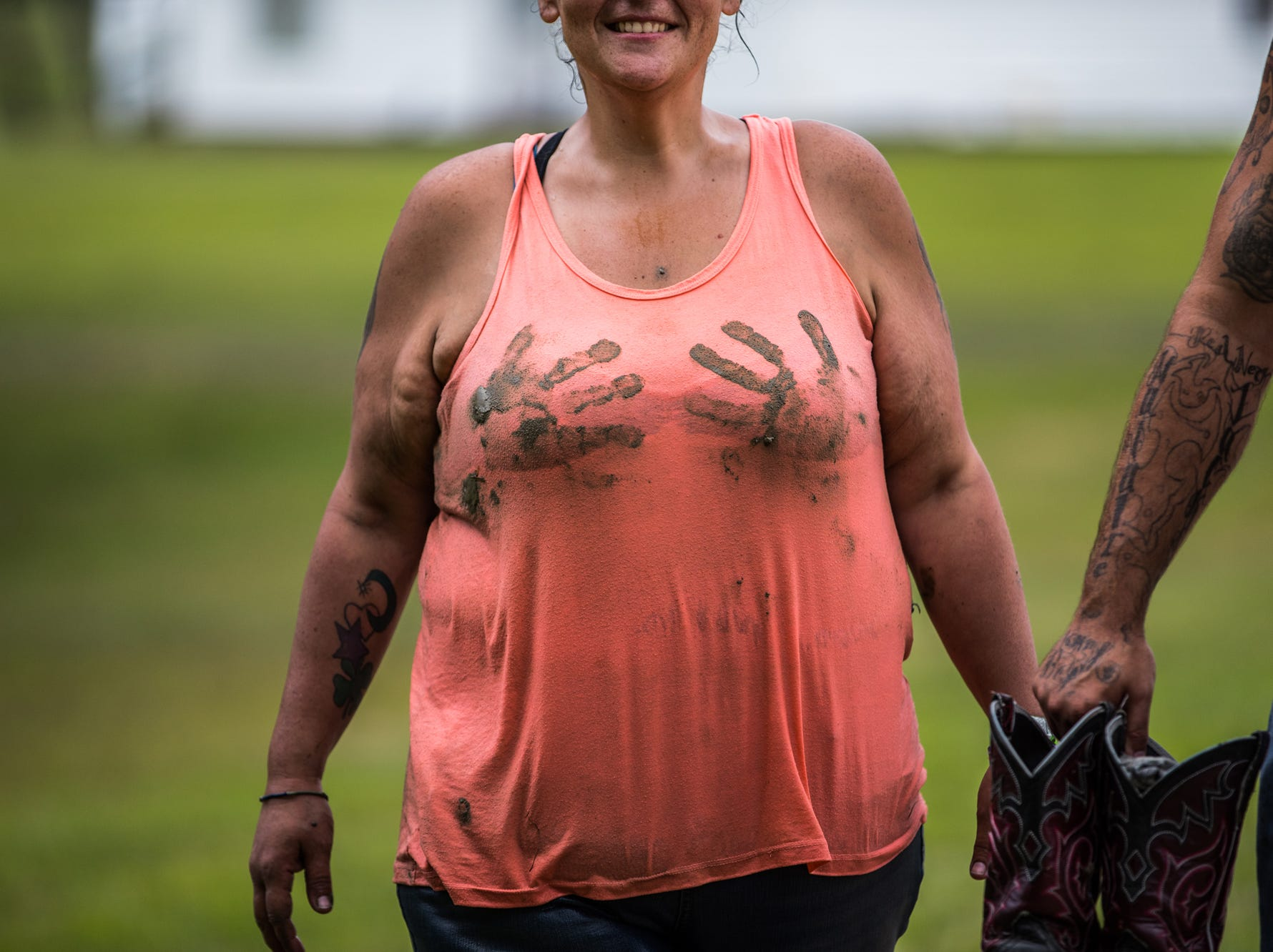 A Redneck Rave participant makes her way along a gravel road near the mud pits at BlackSwan Mudpit in Medora, Ind., on Friday, July 20, 2018.
