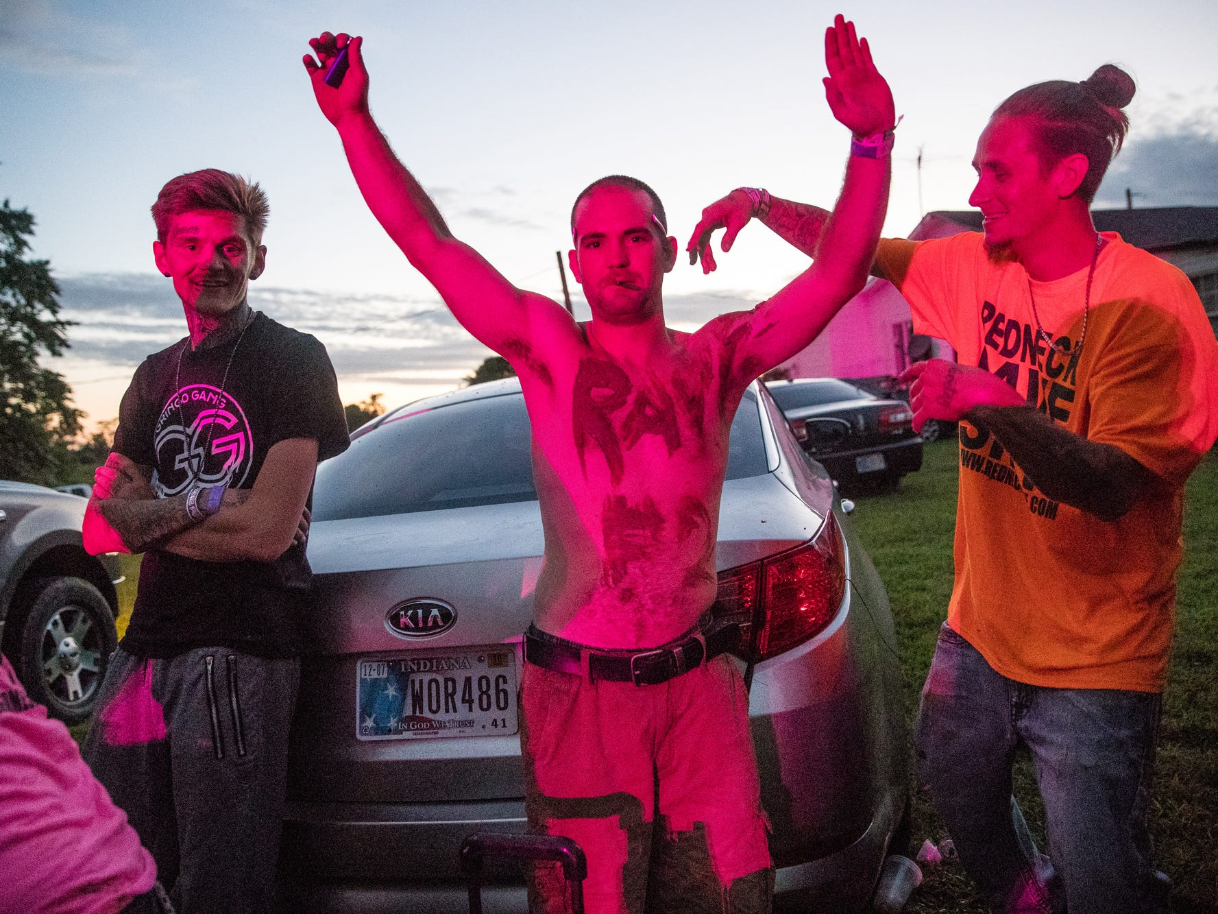 "An attendee pants ""Rave"" on his chest with mud during the Redneck Rave at BlackSwan Mudpit in Medora, Ind., on Friday, July 20, 2018."