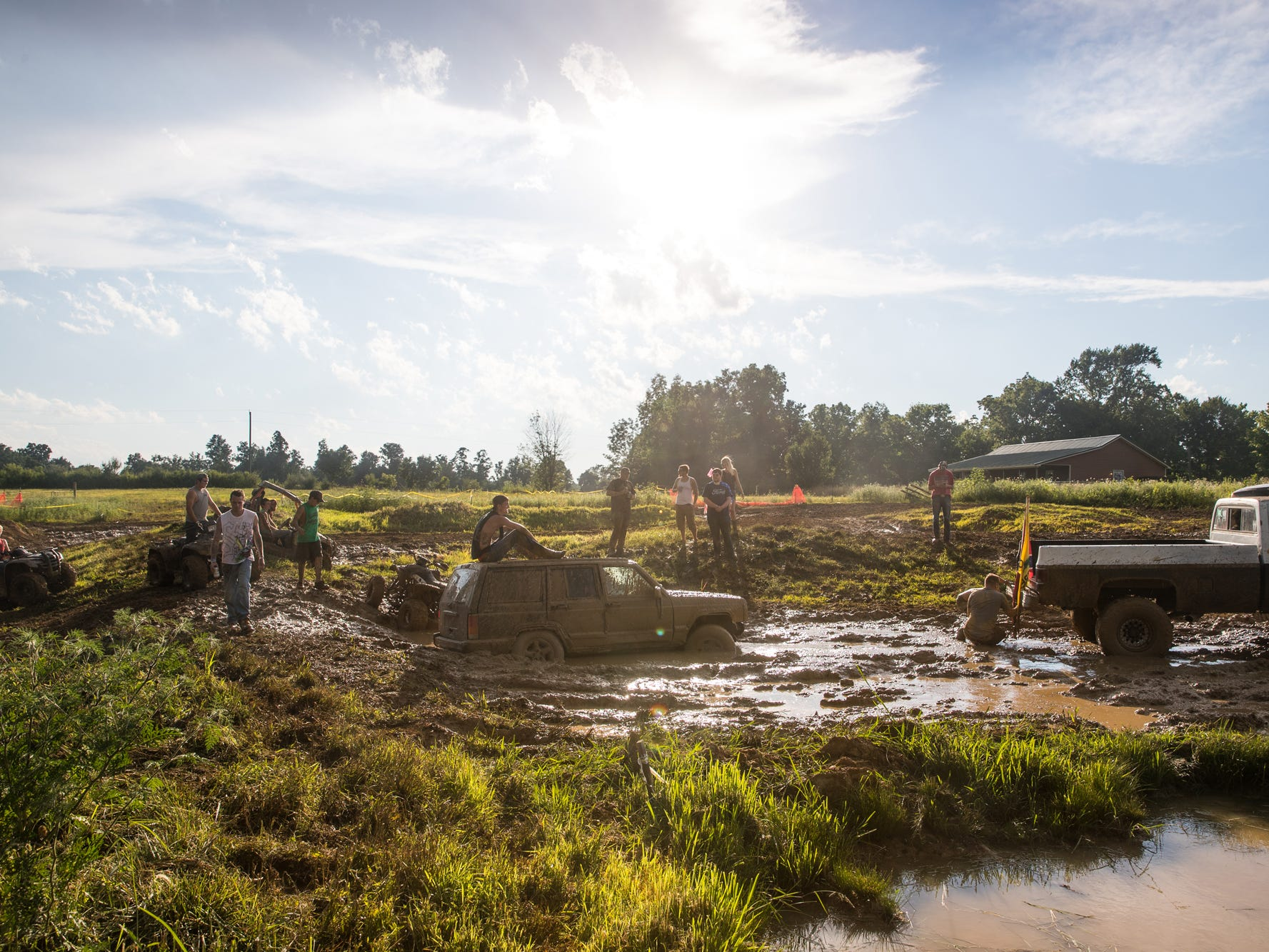 Redneck Rave attendees work to get a stuck Jeep out of a mud pit at BlackSwan Mudpit in Medora, Ind., on Friday, July 20, 2018.