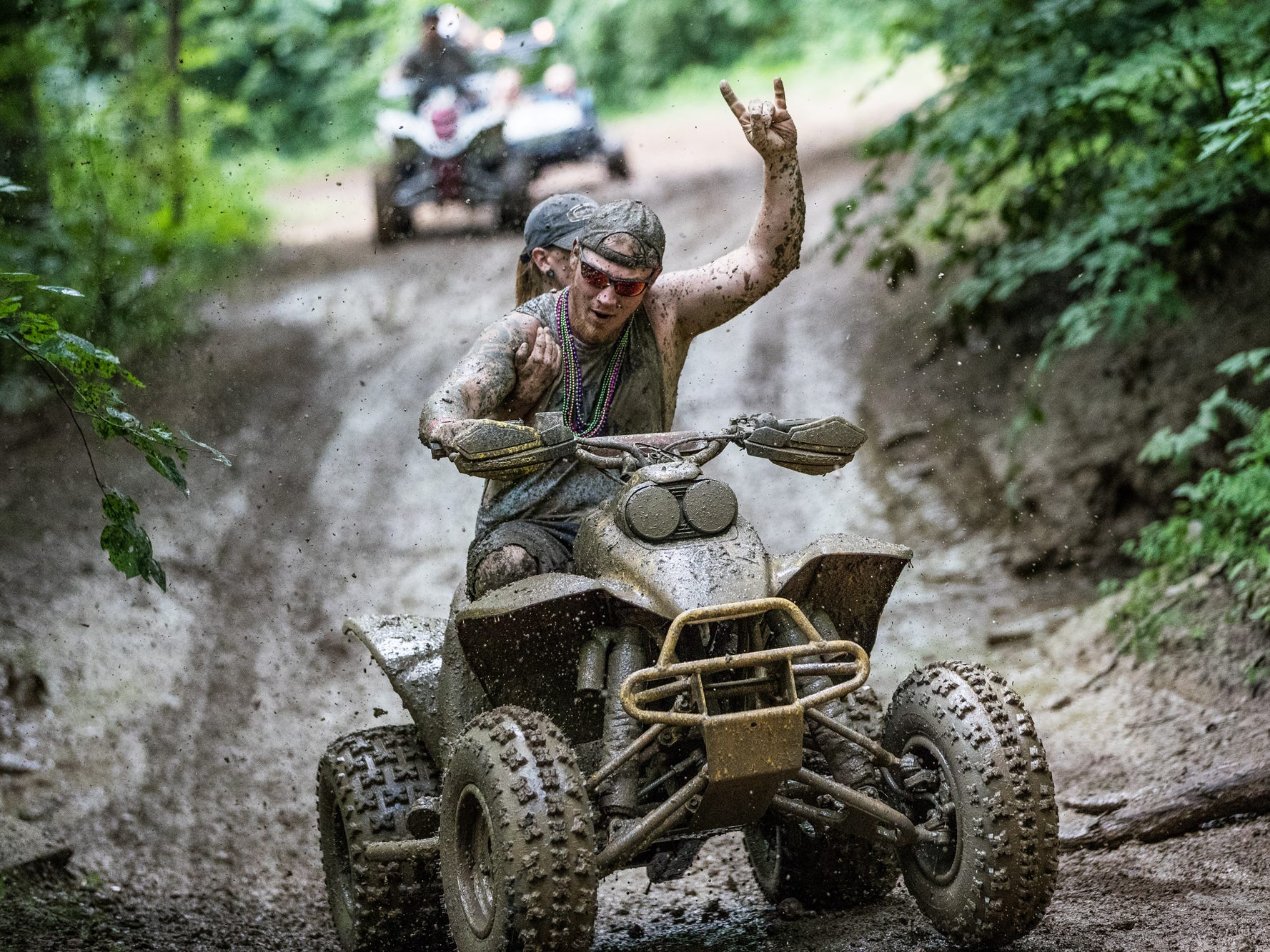 Jarrod Timberman and Paige Skirvin, of Brazil, Ind., ride through the trails of BlackSwam Mudpit in Medora, Ind., during Redneck Rave on Friday, July 20, 2018.