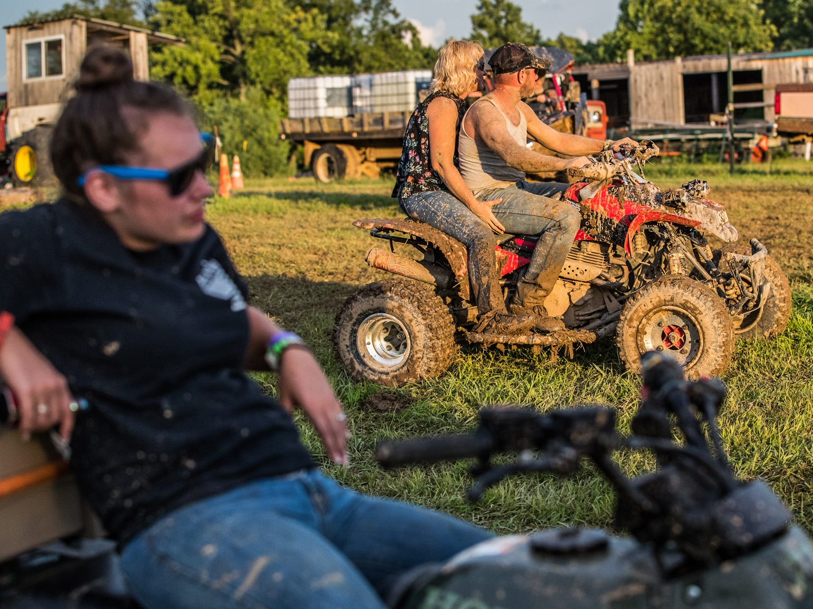 As the sun sets, ATV riders begin to exit the mud pits during the Redneck Rave at BlackSwan Mudpit in Medora, Ind., on Friday, July 20, 2018.