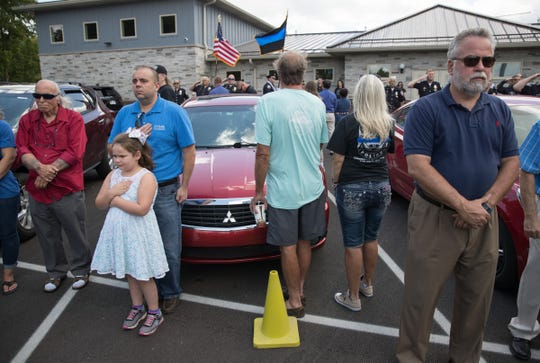 A few of the approximately 100 people on hand for a dedication for a memorial for Aaron Allan, a Southport Police Department officer who was shot and killed during a traffic stop a year eariler, Friday, July 27, 2018.