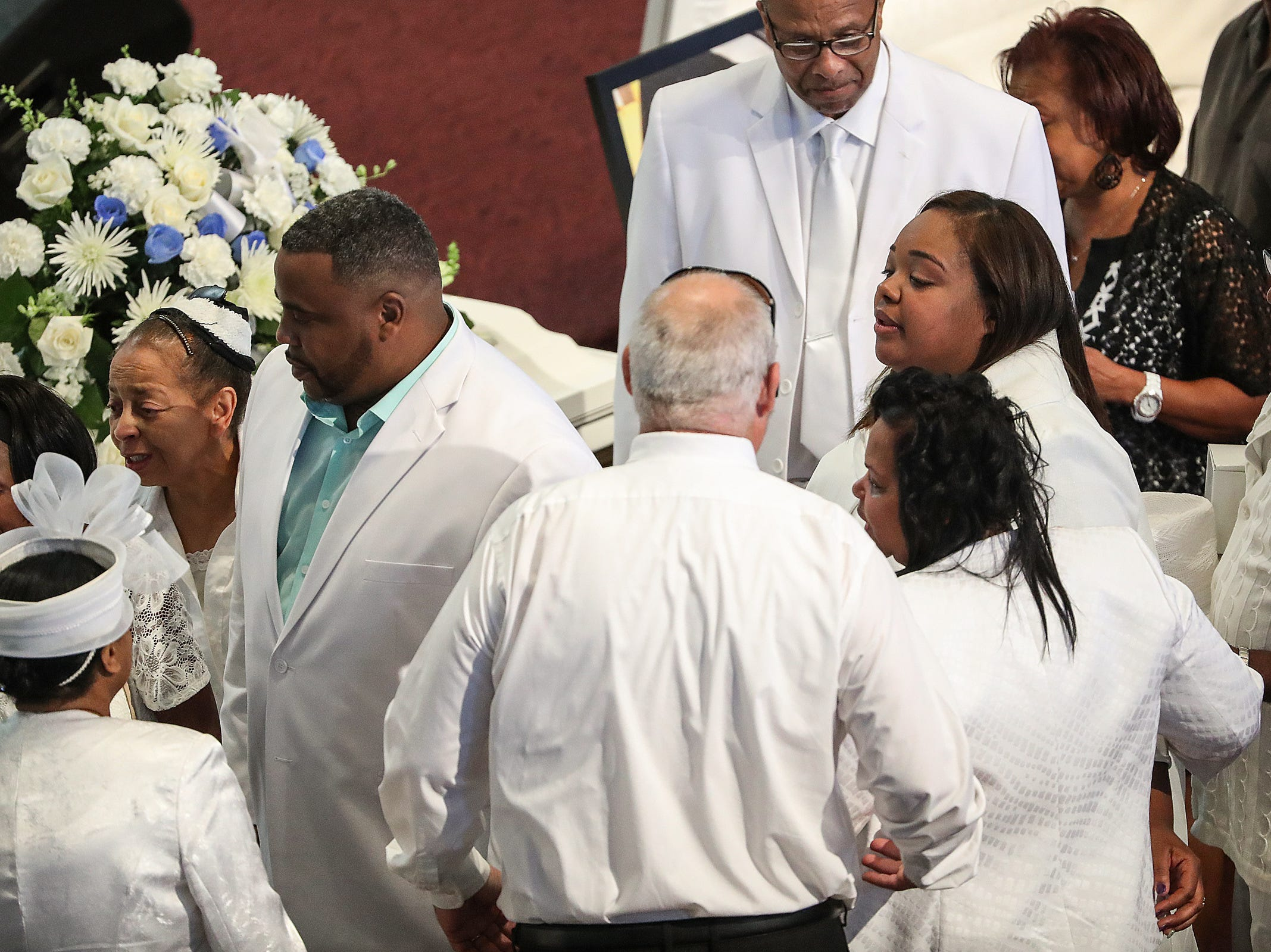Tia Coleman, right, and other family and friends gather for the homegoing service of Tia's husband Glenn Coleman, 40, and children Reece, 9, Evan, 7, and Arya, 1, at Grace Apostolic Church on Friday, July 27, 2018. Seventeen people were killed in the duck boat incident in Branson, Missouri, nine of them were members of the Coleman family.