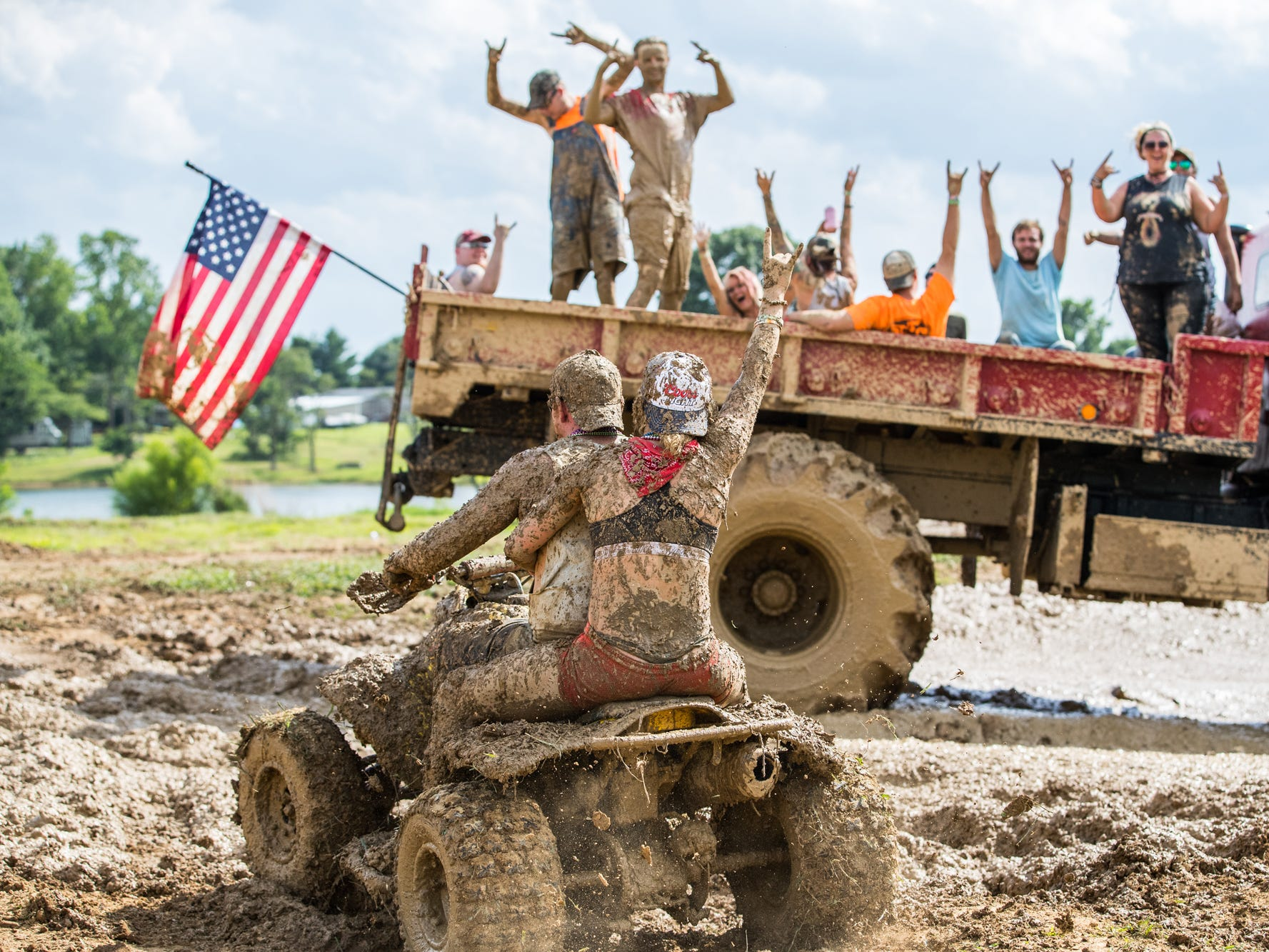 Riders on the back of Dean Keith's red military truck wave to ATV riders Jarrod Timberman and Kate Barton during the Redneck Rave at BlackSwan Mudpit in Medora, Ind., on Friday, July 20, 2018.