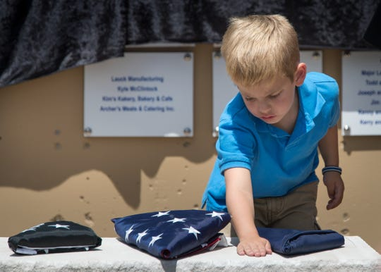 Aaron Allan Jr. touches a stone Friday at a dedication memorial for his father, Aaron Allan, a Southport Police Department officer who was shot and killed during a traffic stop a year earlier.