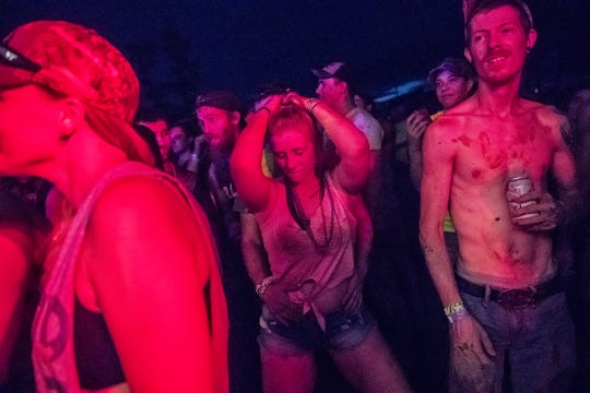 """Two Redneck Rave attendees dance as the music begins at BlackSwan Mudpit in Medora, Ind., on Friday, July 20, 2018. """"We're in a genre of music called country rap,"""" said Justin Stowers, creator of the Redneck Rave. """"I use this platform so the up and coming artists can get the stage time."""""""