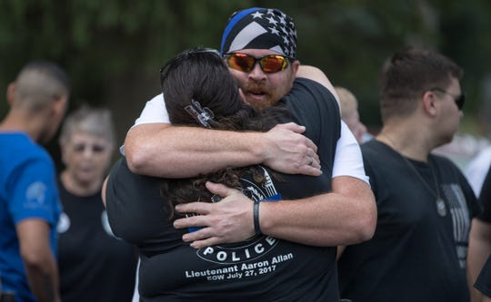 James Berry (right), a former law enforcement officer, hugs another attendee of a dedication for a memorial for Aaron Allan, a Southport Police Department officer who was shot and killed during a traffic stop a year eariler, Friday, July 27, 2018.