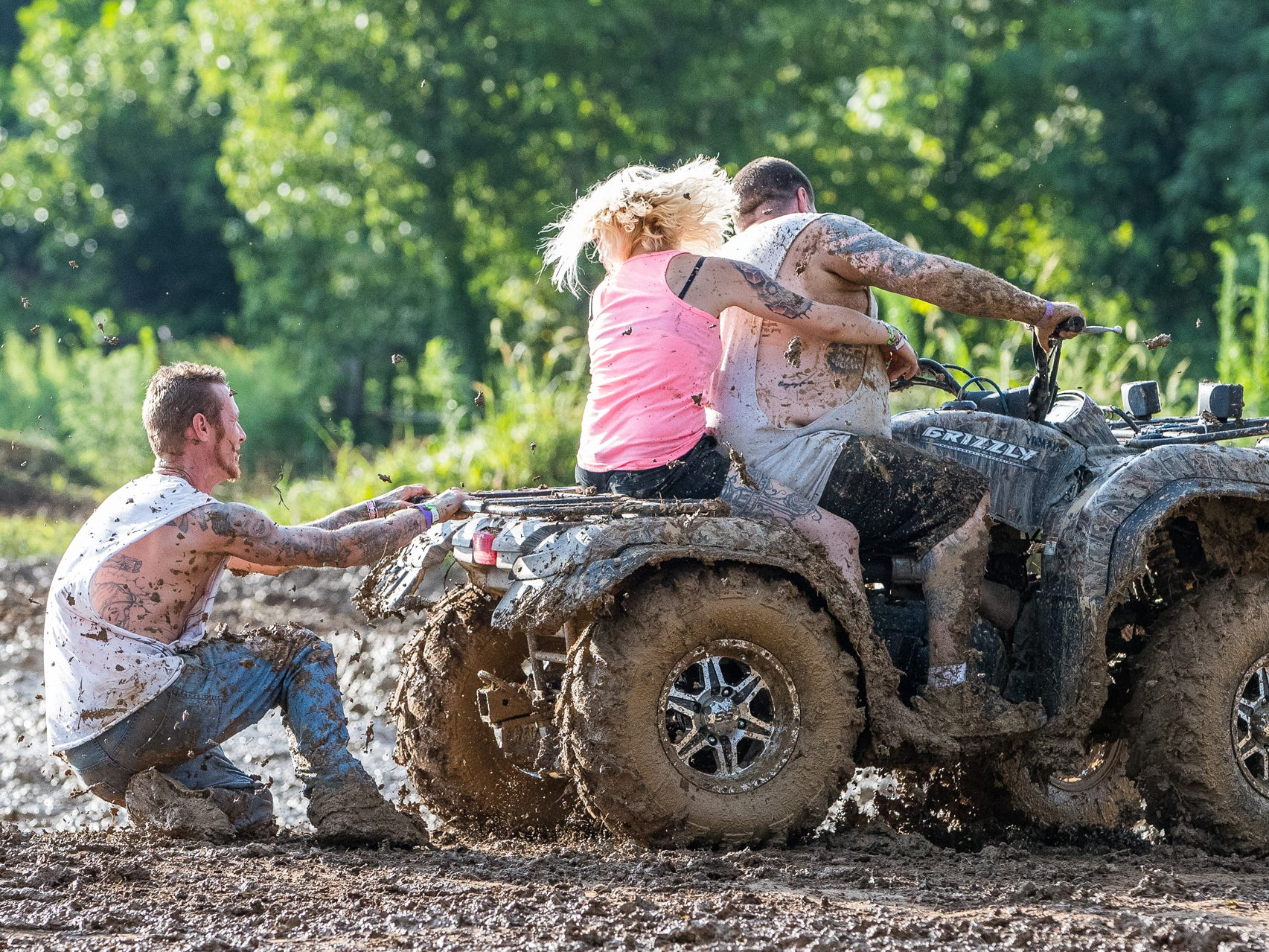 An attendee hangs onto the back of an ATV while getting dragged through the mud during the Redneck Rave at BlackSwan Mudpit in Medora, Ind., on Friday, July 20, 2018.
