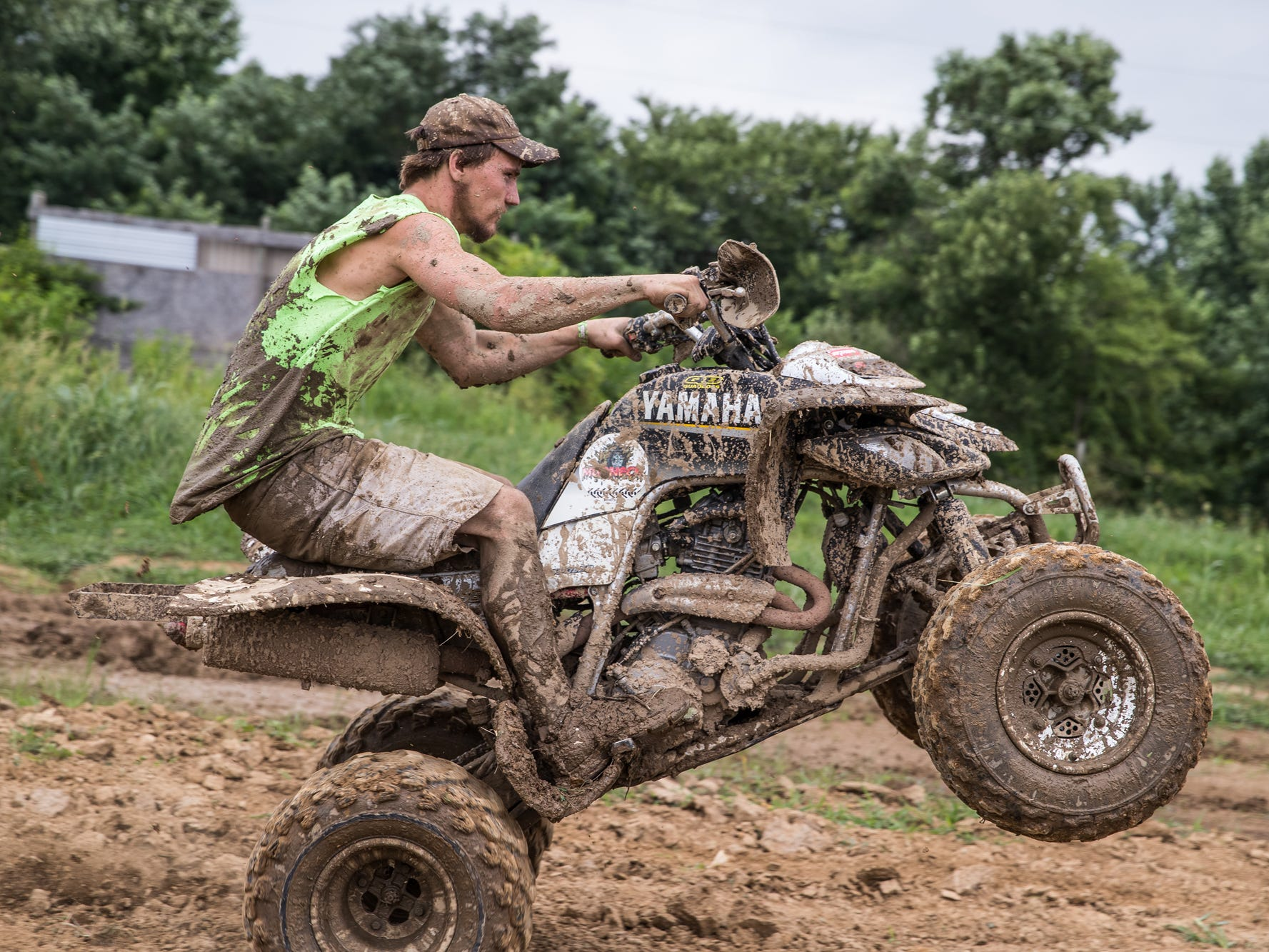 Ethan Taylor, of Middletown, Ohio, pops a wheelie on his ATV during the Redneck Rave at BlackSwan Mudpit in Medora, Ind., on Friday, July 20, 2018.