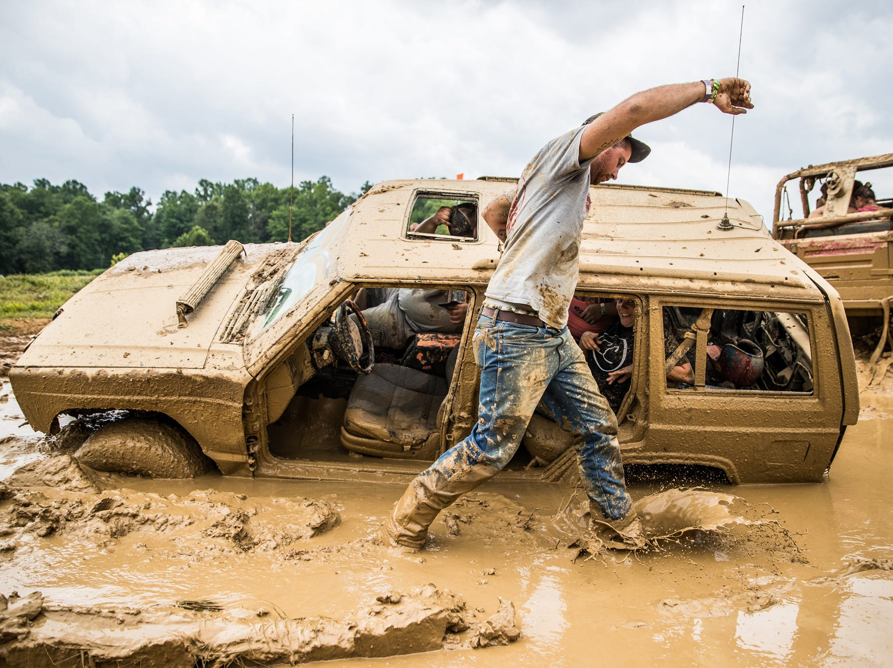 After getting stuck in the mud, a driver wades through a mess to reattac a pull cable to a Jeep Wrangler during the Redneck Rave at BlackSwan Mudpit in Medora, Ind., on Friday, July 20, 2018.