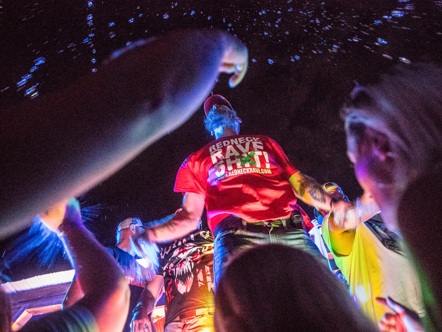"Redneck Rave creator and music artist Justin Stowers performs with other country rap artists during the Redneck Rave at BlackSwan Mudpit in Medora, Ind., on Friday, July 20, 2018. Stowers, a self proclaimed city-boy from Fort Wayne, Ind., started the Redneck Rave in 2016. ""I was working at Arby's and cutting grass. Saved up some money so I could throw a little party,"" he said. ""A buddy came up to me and said 'man, you should throw a county party.' I was like alright, I'll try it.""  The most recent event marks the 19th Redneck Rave."