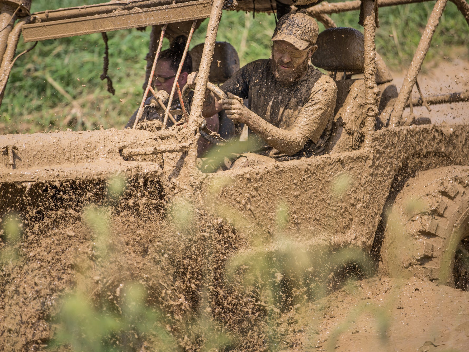 A couple takes a Jeep through a mud pit during the Redneck Rave at BlackSwan Mudpit in Medora, Ind., on Friday, July 20, 2018.