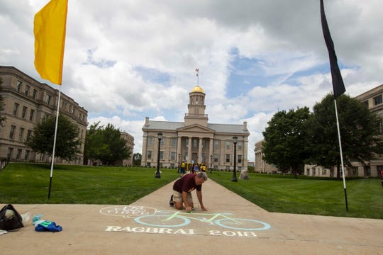 Dean Wicklund, of Coralville, Iowa, finishes up a chalk drawing in front of the Pentacrest while riders make their way into Iowa City for an overnight stop on Friday, July 27, 2018, in eastern Iowa.