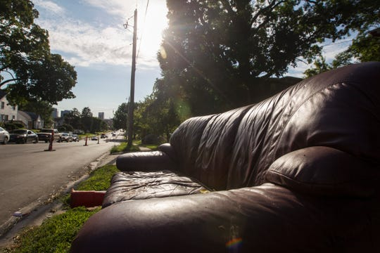 A couch sits along the curb on the corner of Burlington and Governor Streets on Wednesday, July 25, 2018, in Iowa City, Iowa.