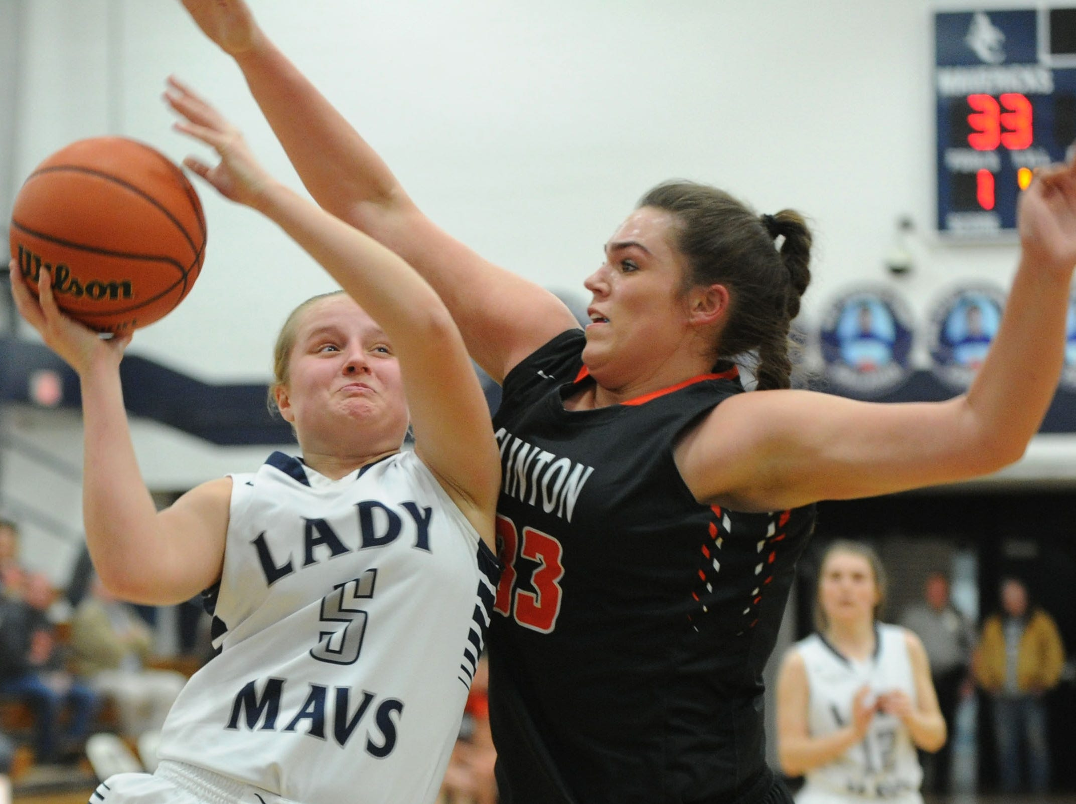 Anderson County High School's Maddie Sickau, 5, attempts a shot while defended by Clinton High School's Kelly Wandell, 33, at a high school girls basketball game at Anderson County High School against Clinton High School on Tuesday, Feb. 16 2016.