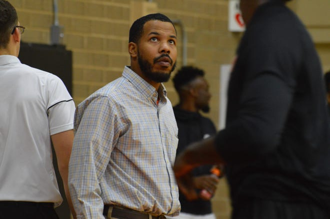 Coach Darren Higgins looks at the scoreboard during a 2017-18 Tusculum basketball game.