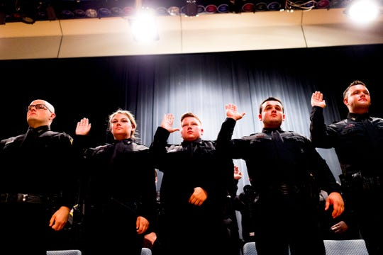 Officers recite the Oath of Honor during a graduation ceremony for school security officers at South-Doyle Middle School in Knoxville, Tennessee on Thursday, July 26, 2018. Knox County Schools graduated twenty-four new officers for the upcoming school year.