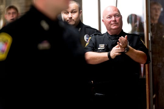A fellow officer applauds graduating officers as they walk into their graduation ceremony for school security officers at South-Doyle Middle School in Knoxville, Tennessee on Thursday, July 26, 2018. Knox County Schools graduated twenty-four new officers for the upcoming school year.
