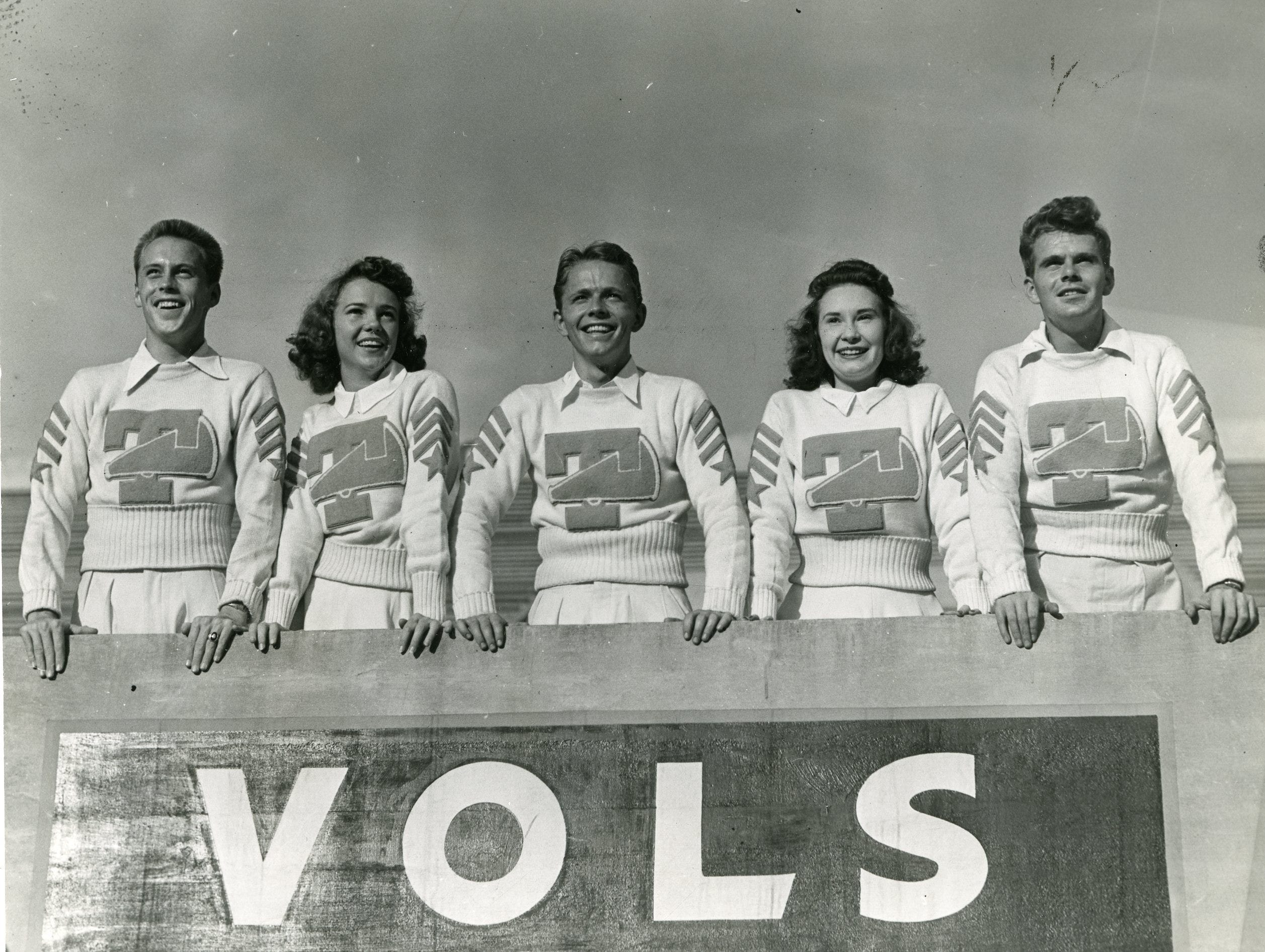 Sporting a cheerleading sweater and ready to cheer on the Vols are 1941 members I.T. Sliger, Helen Childs, head cheerleader Kyle Crowther, Peggy Roberts and Bill Killian.