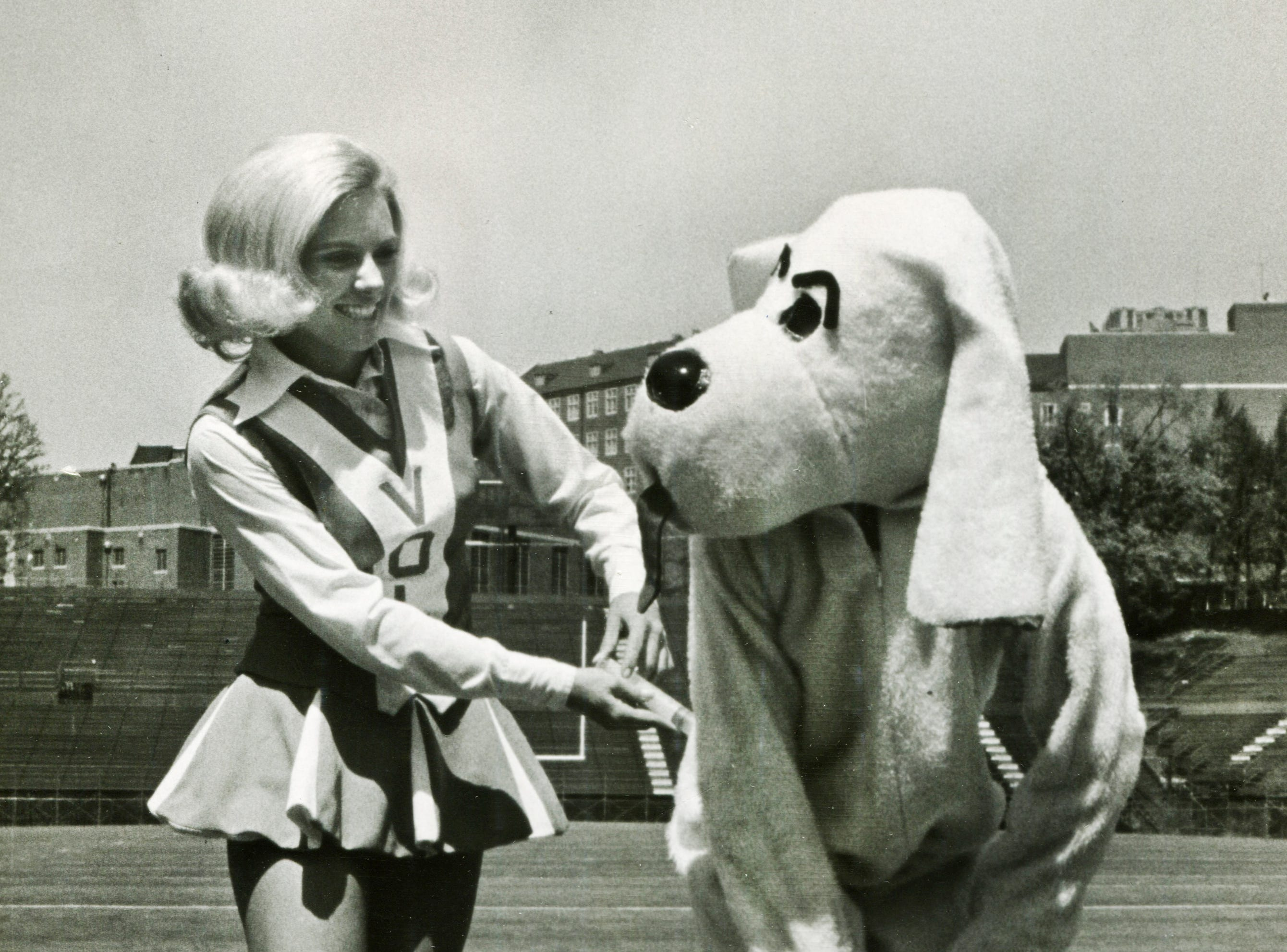 In a photo published April 25, 1971, Tennessee  cheerleader Pat Green pretends to give a rabies shot to Smokey to publicize a County Health Department inoculation clinic for dogs and cats. The good sport wearing the Smokey suit is 12-year-old Chip Brake, son of UT photographer Al Brake.