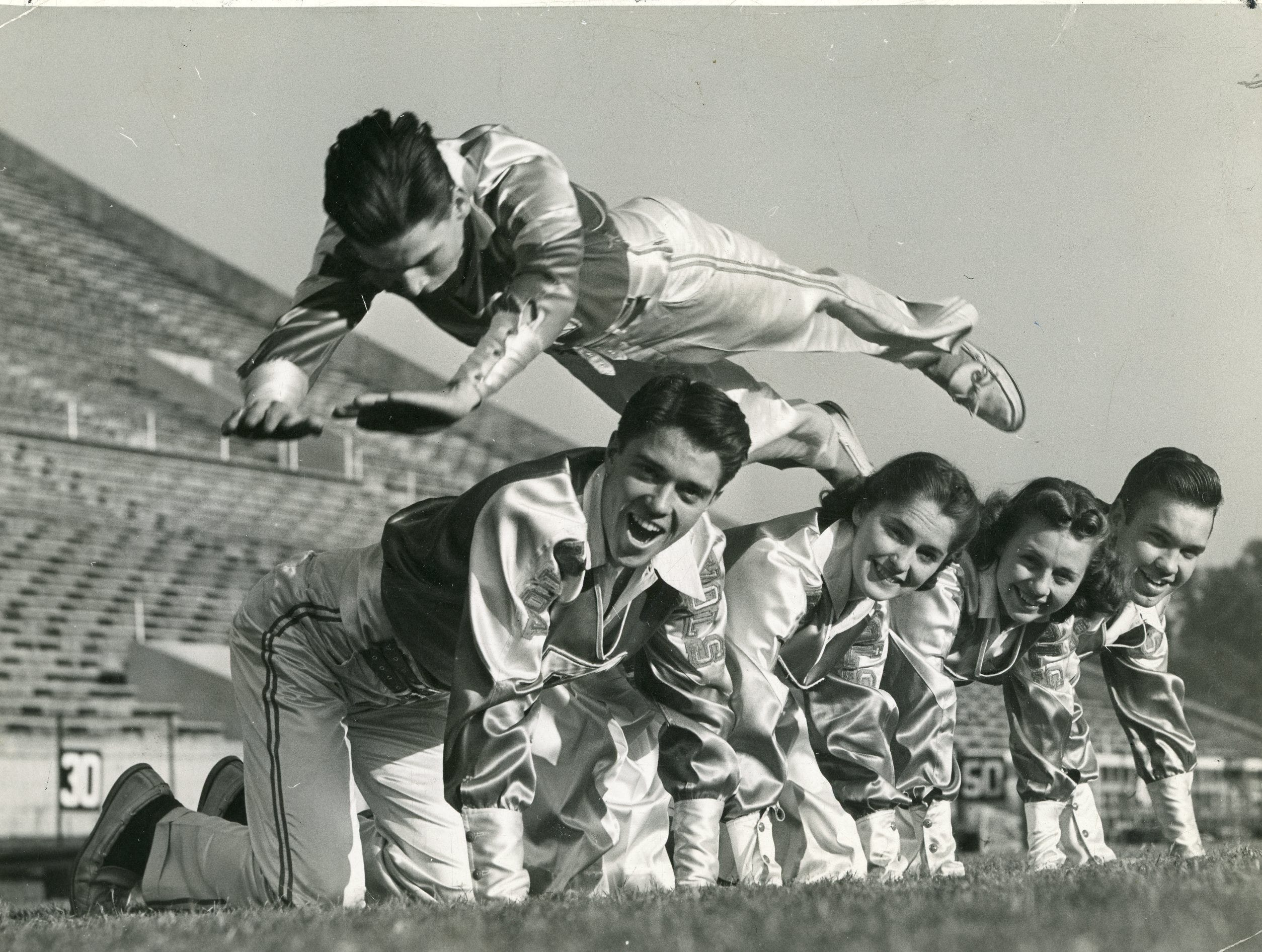 The 1940 UT cheerleaders perform a stunt for the camera. Pictured are Doug Lovejoy (in air), Gaines Stuart, Wilma Rogers, Fay Griffin and Clyde Knisley.