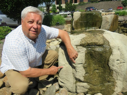 Geological engineer Harry Moore examines a boulder at the Brookview Town Centre fountain park on July 26, 2018