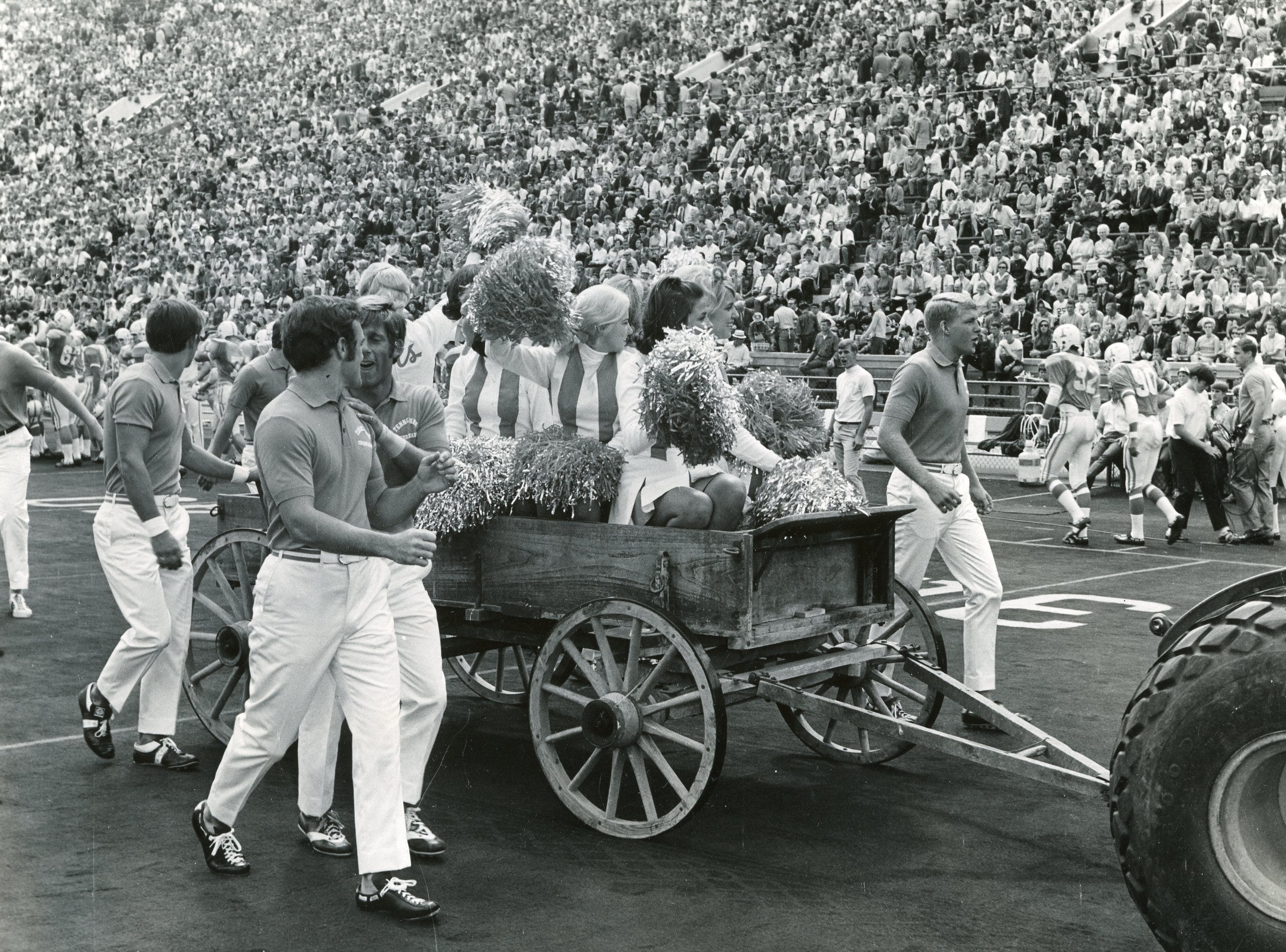 UT cheerleaders ride in the first wagon used by a cheer team. September, 1969.