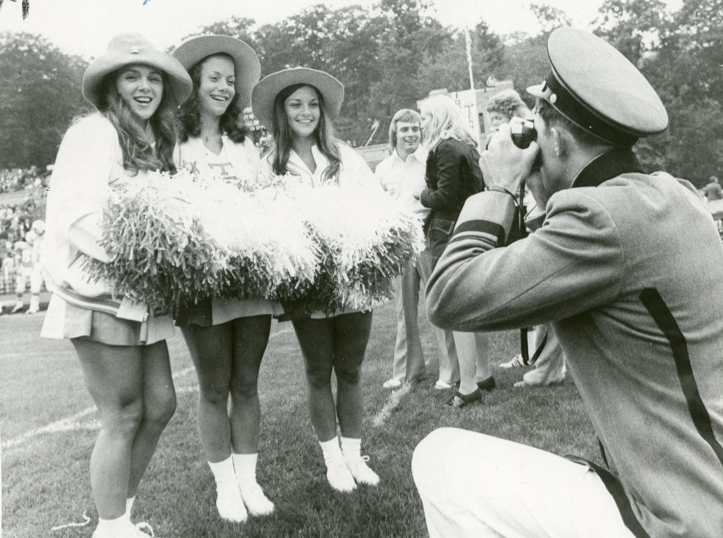 Army cadet Larry Gibbs takes a photo of UT cheerleaders Cyndy Smith, Paula Byrd and Cindy Green, September, 1973.