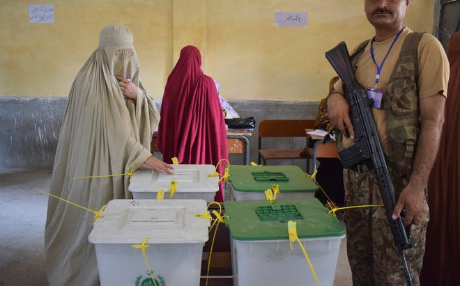 A woman casts her vote at a polling station for the parliamentary elections in Peshawar, Pakistan, Wednesday, July 25, 2018. After an acrimonious campaign, polls opened in Pakistan on Wednesday to elect the country's third straight civilian government in this majority Muslim nation that has been directly or indirectly ruled by its military for most of its 71-year history.(AP Photo/Muhammad Sajjad)