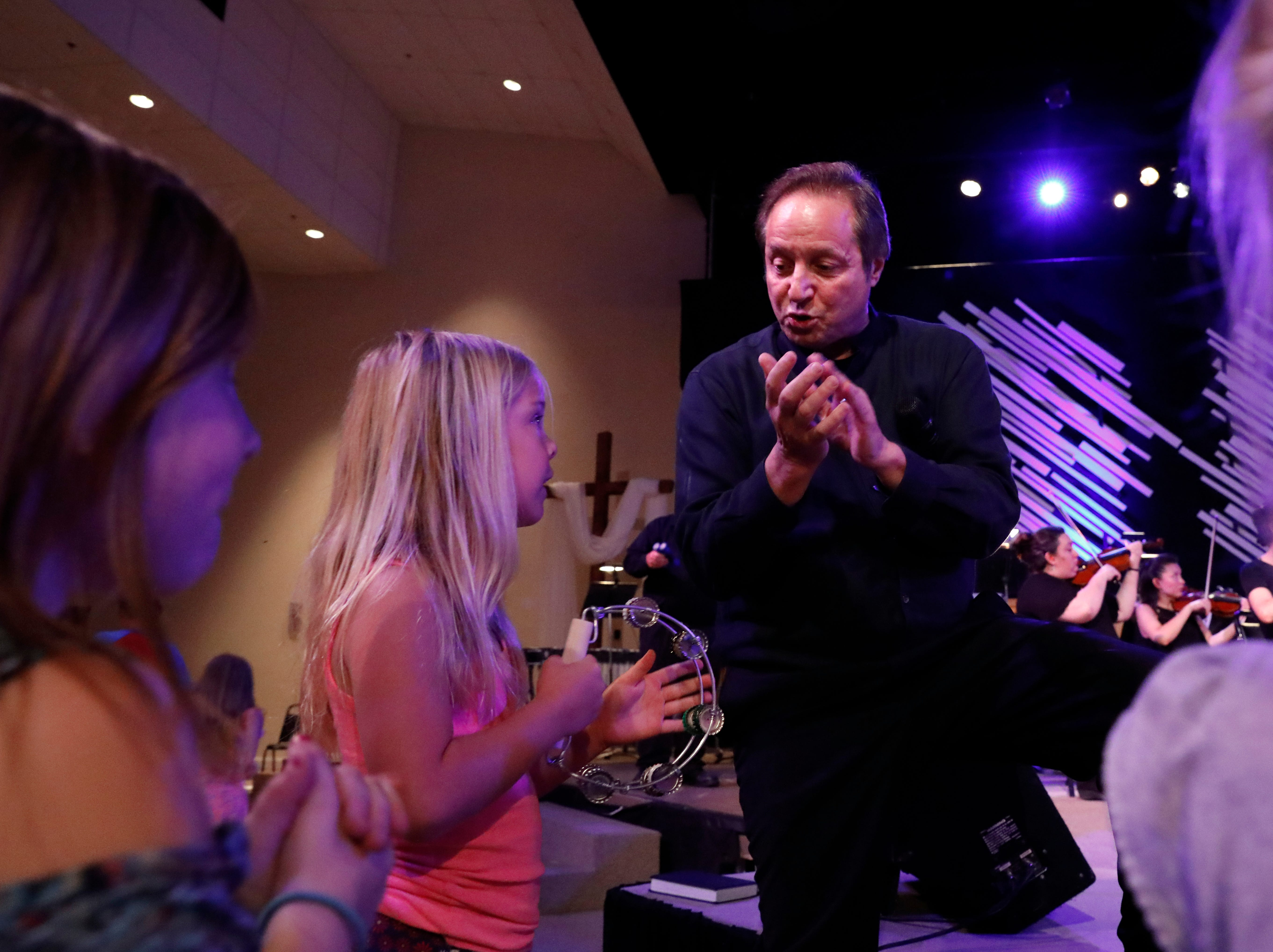 Lancaster Festival Orchestra conductor Gary Sheldon claps in time with children playing tambourines Thursday night, July 26, 2018, at Fairfield Christian Church in Lancaster.