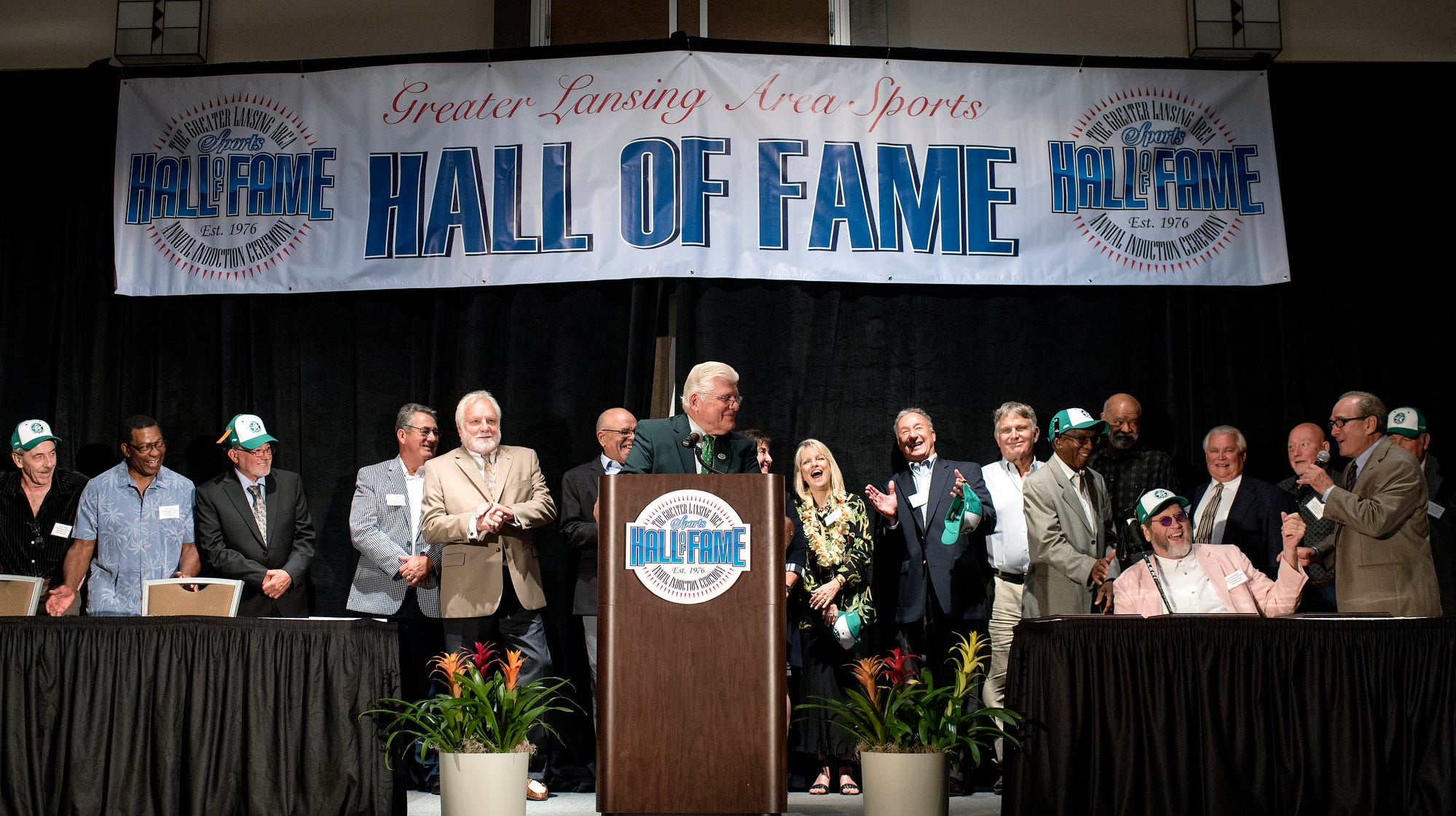 """Coach Robert """"Turf"""" Kauffman, center, is joined by members of the 1970 Lansing All-Stars football team during the 2018 Greater Lansing Area Sports Hall of Fame Induction Ceremony at the Lansing Center on Thursday, July 26, 2018, in downtown Lansing. The team was induced into the hall of fame."""