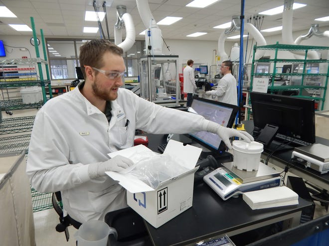 Matt Homstad, a clinical lab scientist, inspects a sample at Exact Sciences Corp. in Madison.