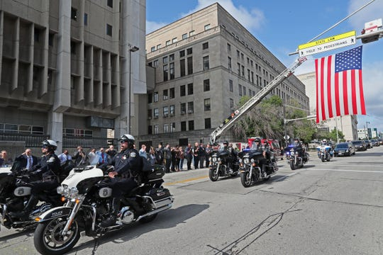 A procession of police motorcycles and other vehicles escorted the hearse carrying the body of fallen police officer Michael J. Michalski as it left the medical examiners office and was taken to the funeral home.