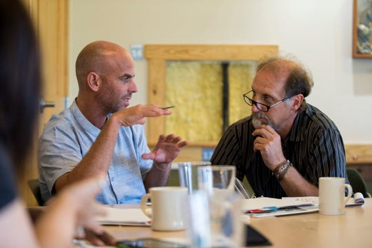 Ken Leinbach (right) listens to Idan Elingold (left), visiting Milwaukee's Urban Ecology Center from Israel. Elingold is discussing his banana farm and how he wants to change and improve it by using the tools he's learning from Leinbach.