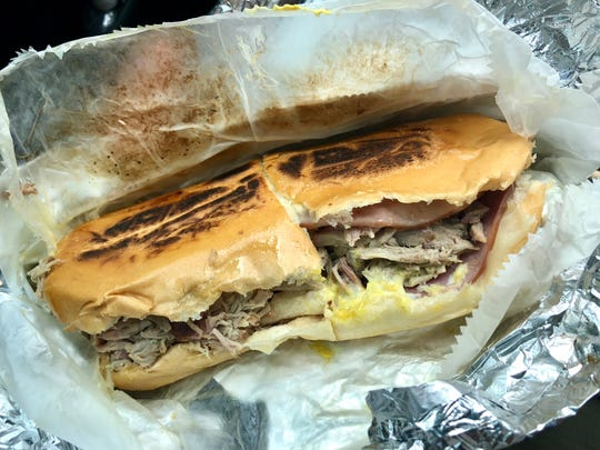 A Cuban sandwich with sliced ham, pulled pork, Swiss cheese, pickles, mayo and mustard between Cuban bread.