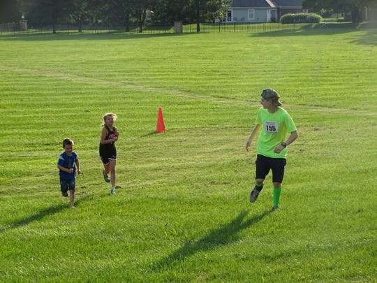 Stephen Epps, 13, of Utica, encourages his brother Sabe Epps, 4, and Evie Bone, 10, of Newark, to reach the finish of the fun run Thursday during the Bryn Du Summer Cross Country Series.