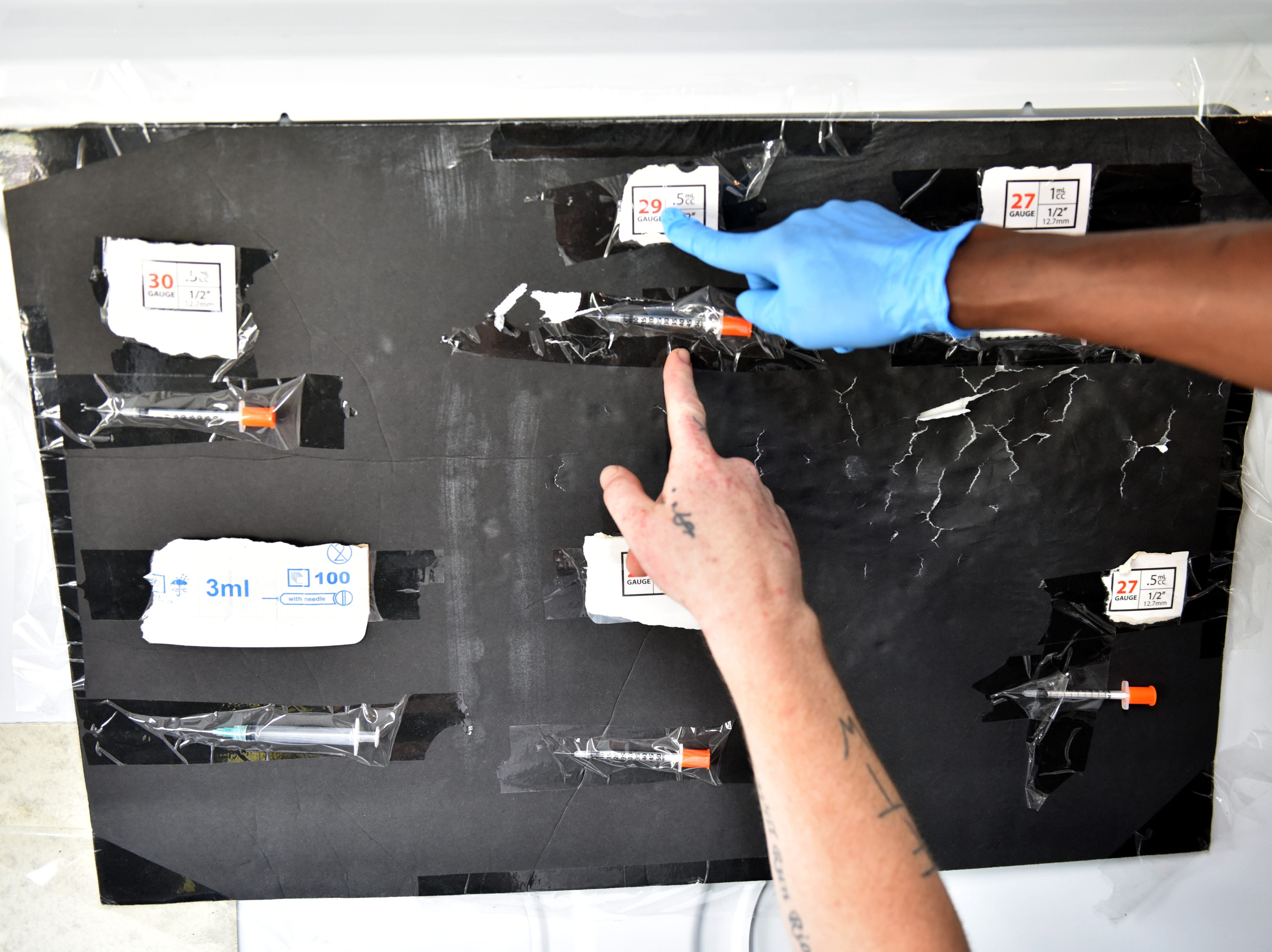 A client points to syringe he would like to have for his exchange. A van parked in the Walgreen's parking lot provides clean needles in exchange for dirty ones twice a week in Paterson on Friday July 27, 2018. For every used syringe brought in, the harm reduction specialists with Hyacinth Foundation provides a new sterile syringe. The van is stocked with syringes of different sizes, alcohol wipes, constriction bands, cooking cups, water, strips to test for fentanyl, and other products to safely inject heroin.