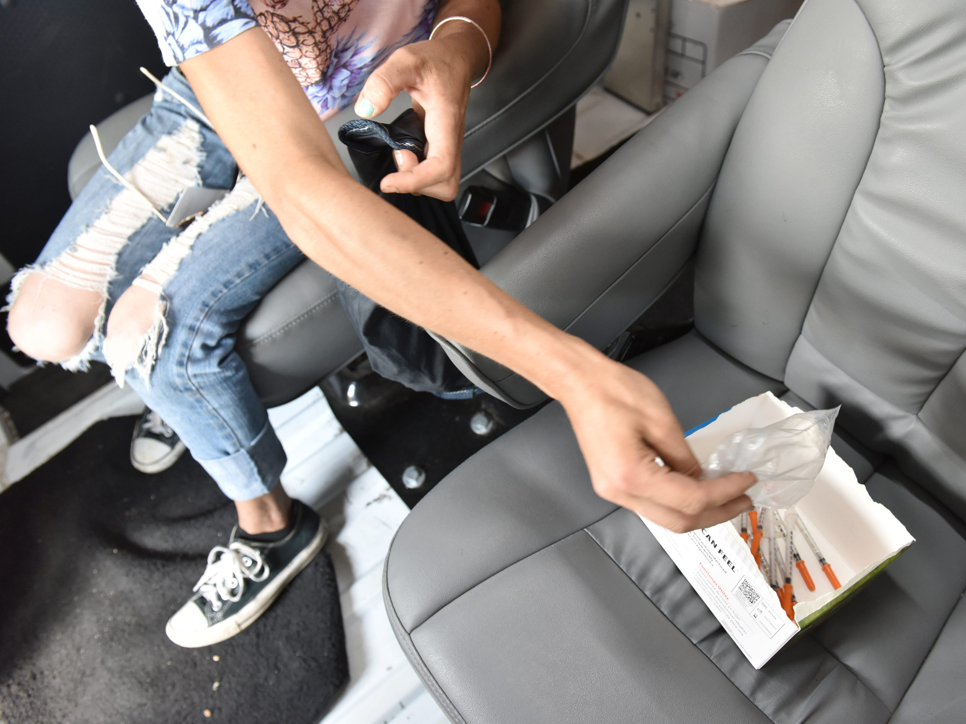 A client drops used syringes into a box to be exchanged. A van parked in the Walgreen's parking lot provides clean needles in exchange for dirty ones twice a week in Paterson on Friday July 27, 2018. For every used syringe brought in, the harm reduction specialists with Hyacinth Foundation provides a new sterile syringe. The van is stocked with syringes of different sizes, alcohol wipes, constriction bands, cooking cups, water, strips to test for fentanyl, and other products to safely inject heroin.