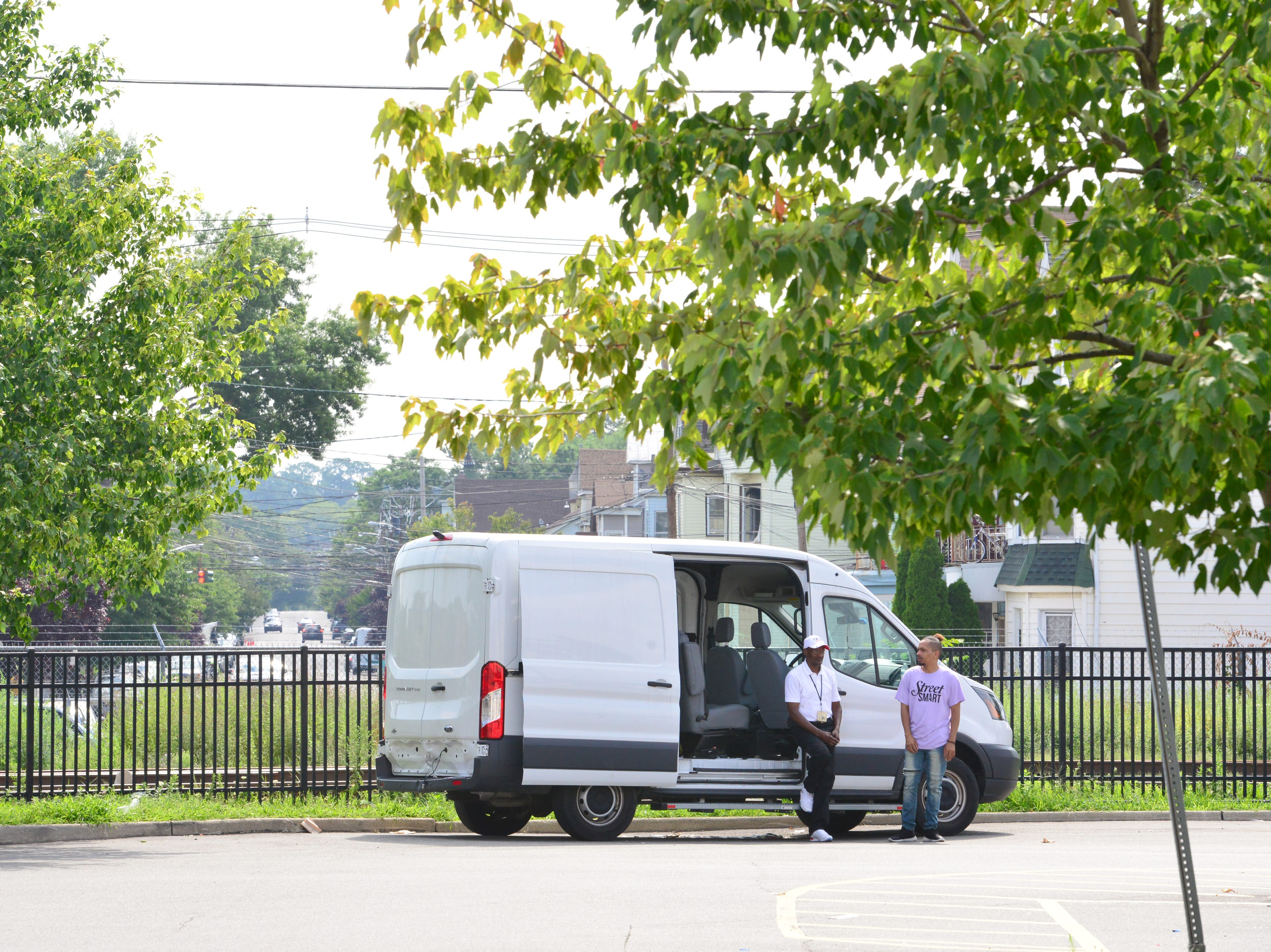 From left, Ralph Henderson and Railen Henderson, no relation, are harm reduction specialists, wait by the van for clients to exchange syringes. A van parked in the Walgreen's parking lot provides clean needles in exchange for dirty ones twice a week in Paterson on Friday July 27, 2018. For every used syringe brought in, the harm reduction specialists with Hyacinth Foundation provides a new sterile syringe. The van is stocked with syringes of different sizes, alcohol wipes, constriction bands, cooking cups, water, strips to test for fentanyl, and other products to safely inject heroin.