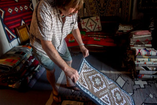 Mark Winter examines a rug made by Marjorie Benallie Thursday at the Toadlena Trading Post and Weaving Museum in Toadlena.