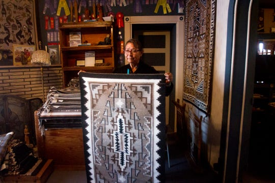 Rose Barber displays her rug Thursday at the Toadlena Trading Post and Weaving Museum in Toadlena.