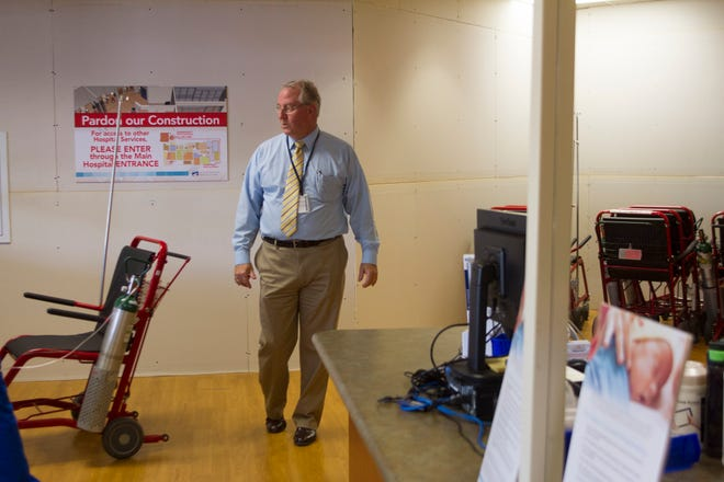 Todd Bille, vice president of strategic planning and business development at San Juan Regional Medical Center, points out a temporary wall, Friday as a renovation project inside the emergency room's lobby area continues at San Juan Regional Medical Center in Farmington.