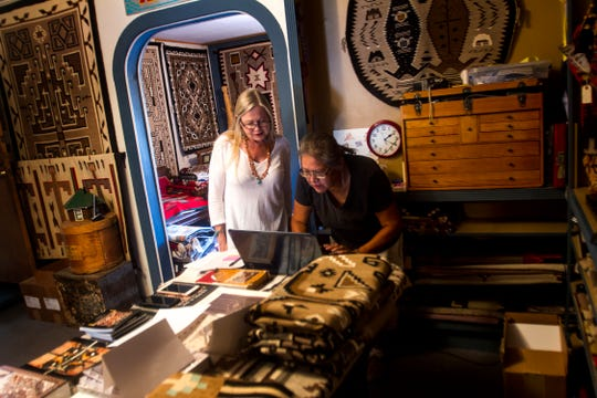 Linda Winter, left, and store manager Delores Brown look over the rug inventory Thursday at the Toadlena Trading Post and Weaving Museum in Toadlena.