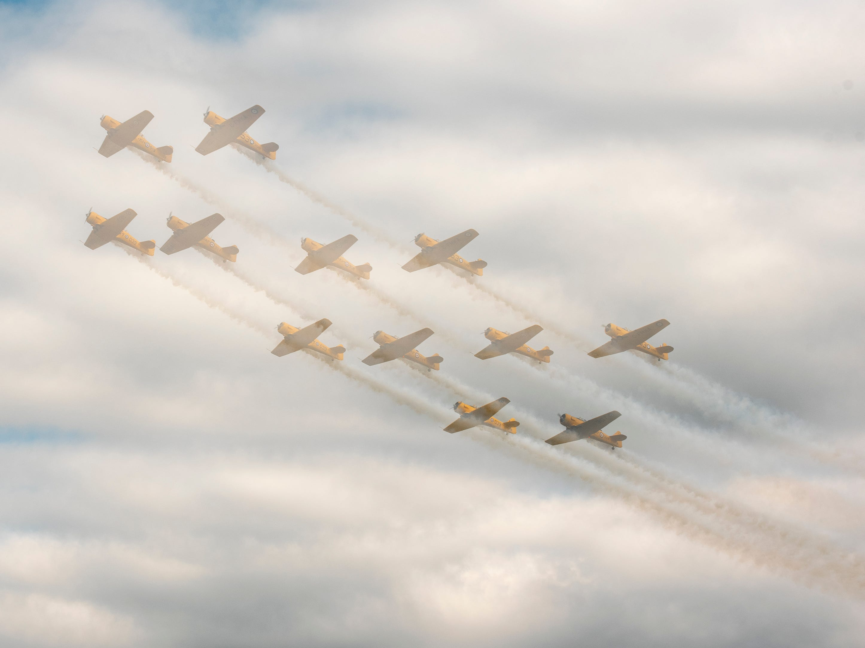 In this multiple exposure photo, the Canadian Harvard Aerobatic Team flies over the runway during the afternoon air show at AirVenture in Oshkosh, Wis., on Thursday, July 26, 2018. All four pilots are from Ontario.