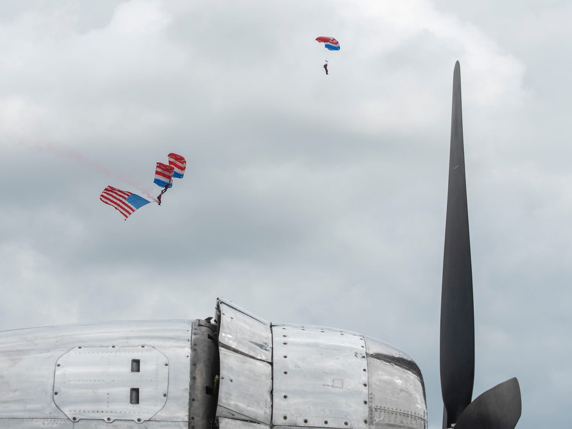 Skydivers float to the ground with an American flag to signify the beginning of the afternoon airshow as seen behind a Boeing B-29 parked in Boeing Plaza at AirVenture in Oshkosh, Wis., on Thursday, July 26, 2018.