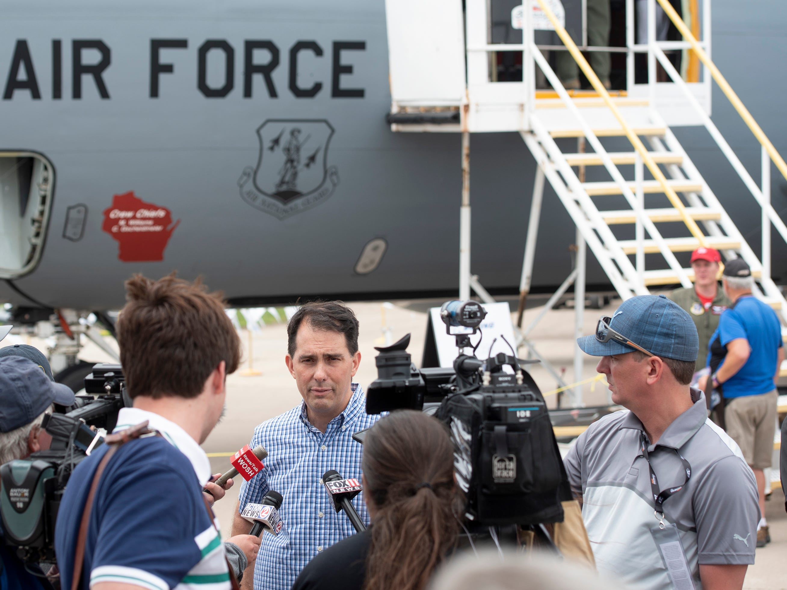 Gov. Scott Walker speaks to members of the press in Boeing Plaza at AirVenture in Oshkosh, Wis., on Thursday, July 26, 2018. Walker toured the 128 Air Refueling Wing behind him before meeting with the press.