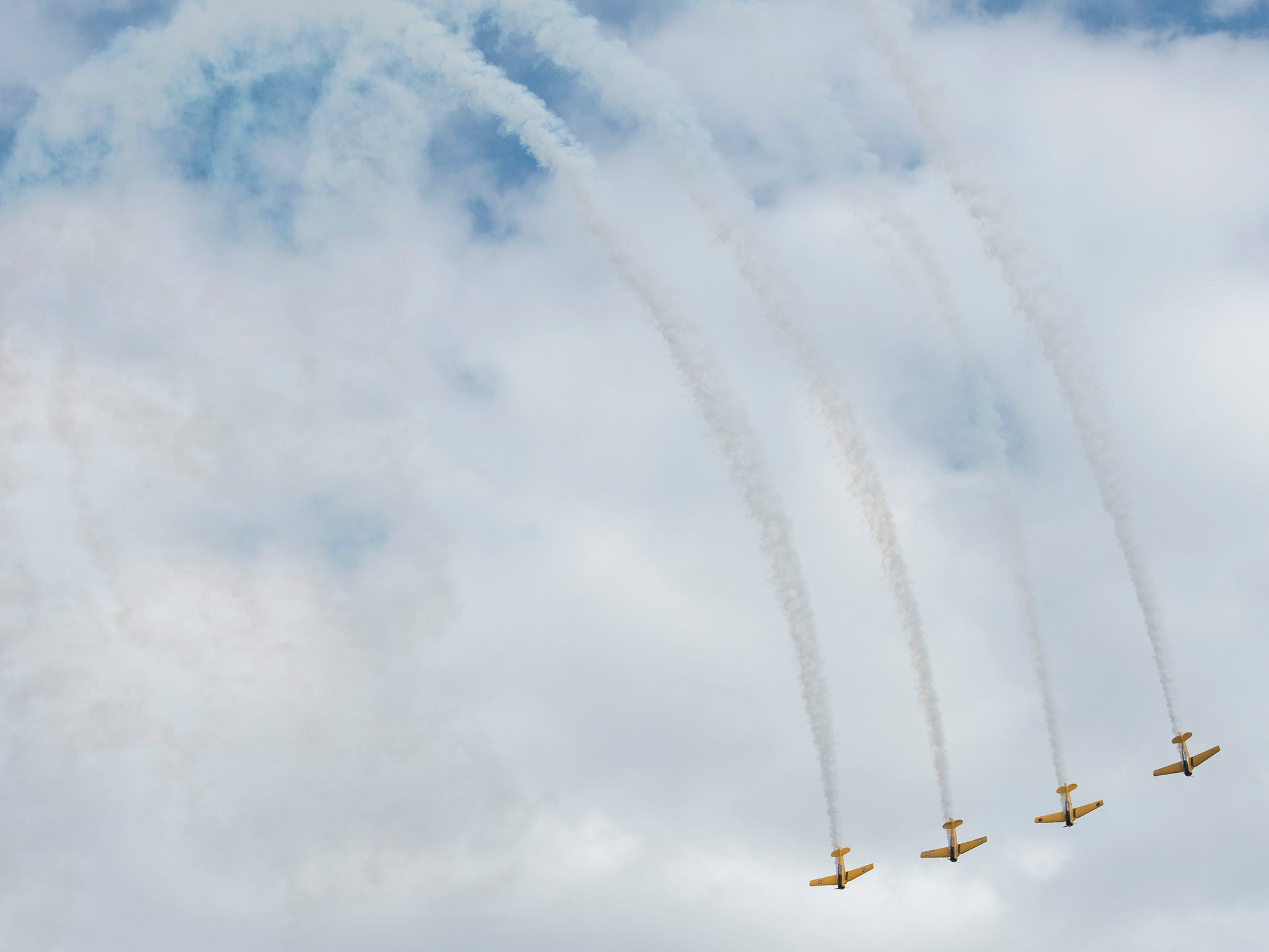 The Canadian Harvard Aerobatic Team flies downward after completing a sharp turn during the afternoon air show at AirVenture in Oshkosh, Wis., on Thursday, July 26, 2018. The team flies as a tribute to World War II veterans.