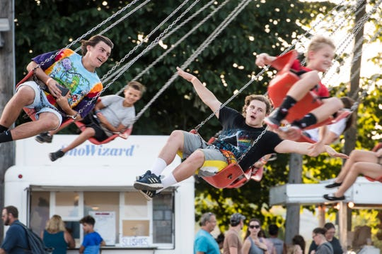 Tommy Morris holds his arms out while enjoying a swing ride with his friend, Nathan Hawkins (far left), at the Pleasant Hill Fire Company carnival on July 26, 2018.