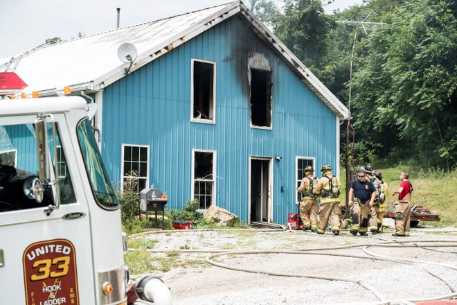 Firefighters work the scene of a residential house and barn fire in Berwick Township on Friday, July 27, 2018.