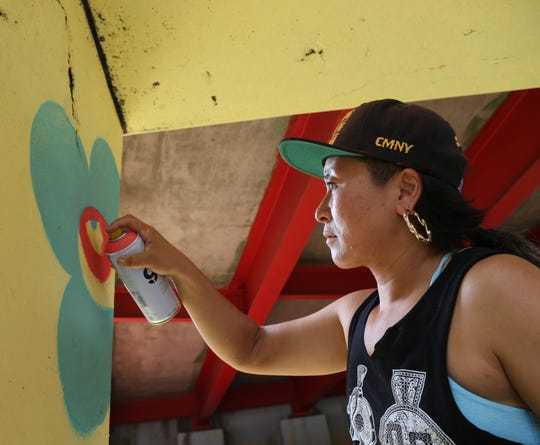 "Risa Tochigi, ""Boogie"" of BoogieREZ, works on their mural on the Route 9 Underpass at Main Street in the City of Poughkeepsie on July 27."